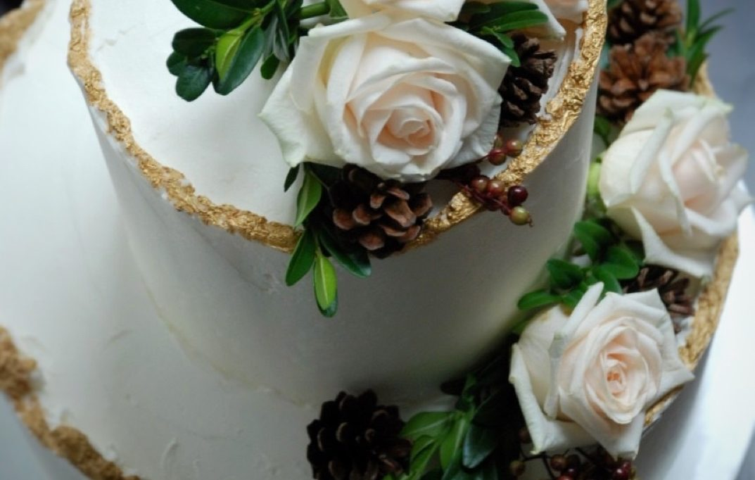 Wedding cake winter theme with wavy gold edges, roses and pine cones
