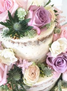 Semi naked wedding cake decorated with summer flowers