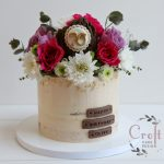 Semi naked 70th birthday cake with fresh flowers and fondant bark