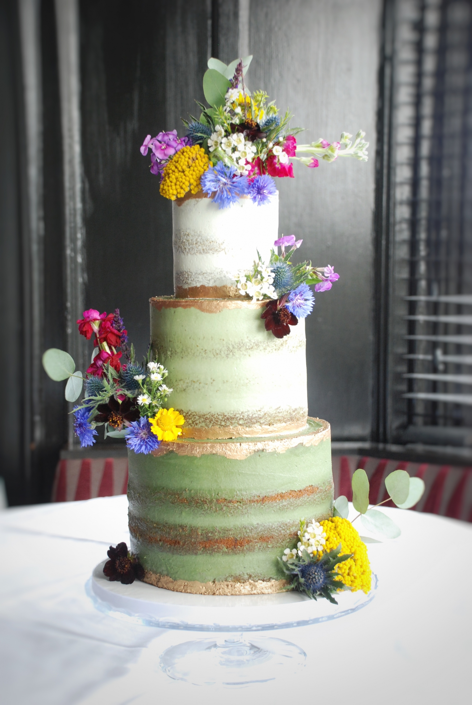 Semi naked green wedding cake with wildflowers